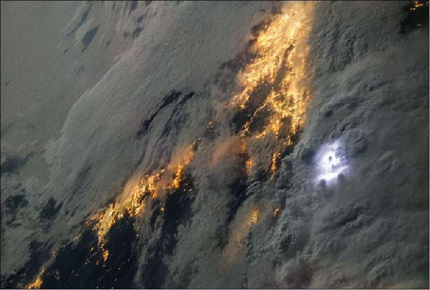 Cette image prise de l'ISS au-dessus de la Californie montre la foudre comme une lueur blanche sur le côté droit à partir du centre de l'image. Les zones éclairées en jaune sous les nuages sont les régions densément peuplées de Los Angeles et de San Diego visibles grâce à l'éclairages publics (Crédit : NASA, ISS036-E-022863, 21 juillet 2013).
